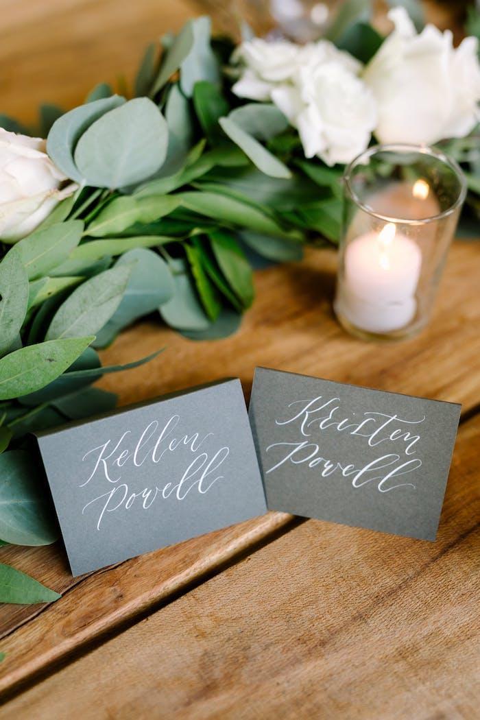 Schöne Idee für Hochzeit Tischdeko, weiße Rosen und Duftkerzen, graue Zettel mit den Namen der Gäste