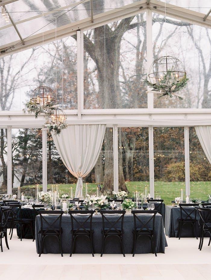 Stilvolle Tischdekoration für Hochzeit, graue Tischdecken, weiße Blumen und Kerzen, große runde Kronleuchter