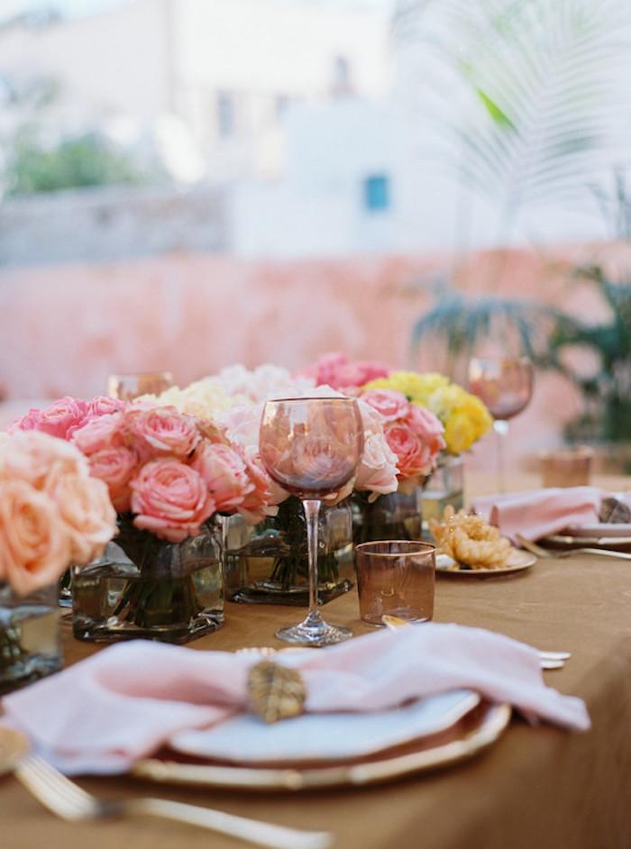 Tischdeko in warmen Farben, kleine Rosensträuße, Gläser aus Kristall und rosafarbene Servietten