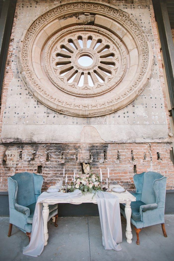 Hochzeit Tischdeko in Landhaus, weißer Holztisch mit Altersspuren, weiße Rosen und Kerzen, blaue Sessel