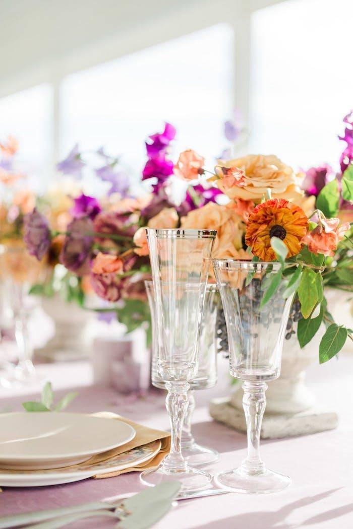 Tischdeko in warmen Pastellfarben, Weingläser mit silbernem Rand, viele Blumen
