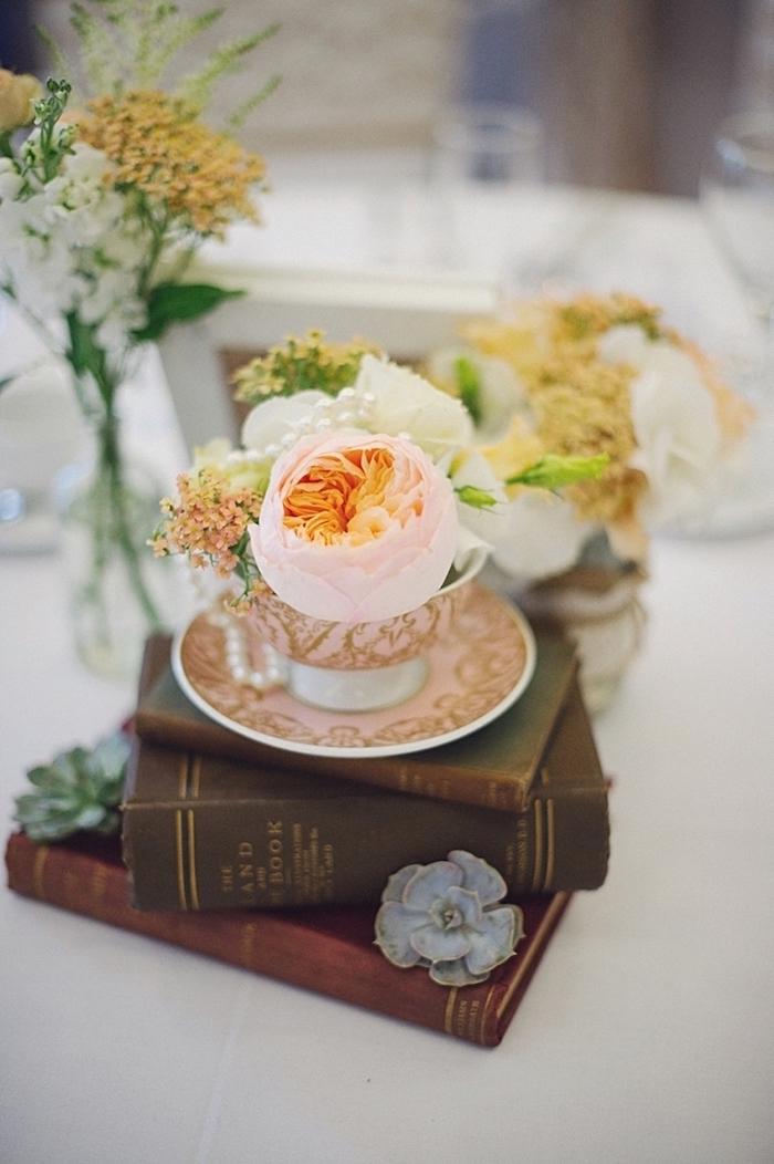 Prachtvolle Tischdekoration für Hochzeit, Blumen in Porzellantassen auf antiken Büchern