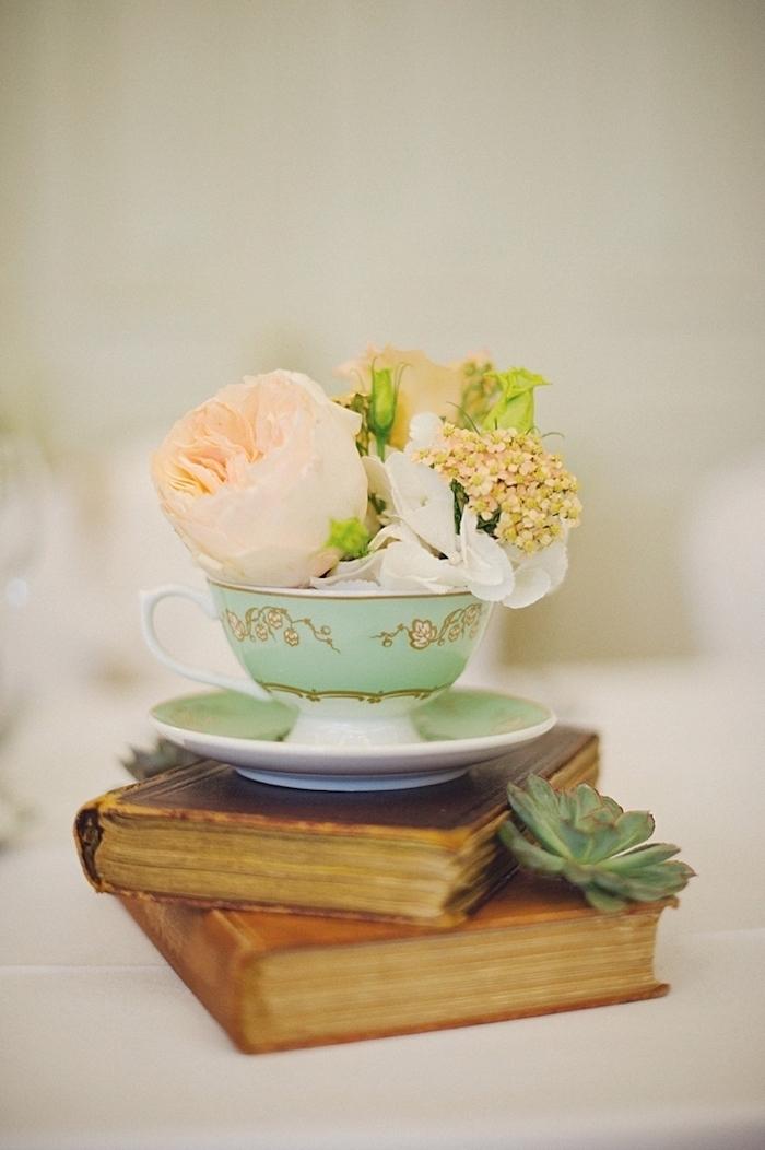 Blüten in Porzellantasse auf antiken Büchern, kreative und romantische Idee für Hochzeitsdeko