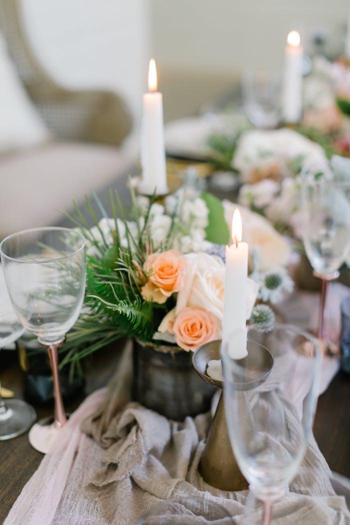 Stilvolle Tischdekoration für Hochzeit, weiße Kerzen und kleine Blumensträuße