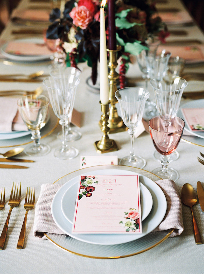 Menü mit Blumenmuster, goldene Kerzenhalter, Gläser aus Kristall, weiße Tischdecke