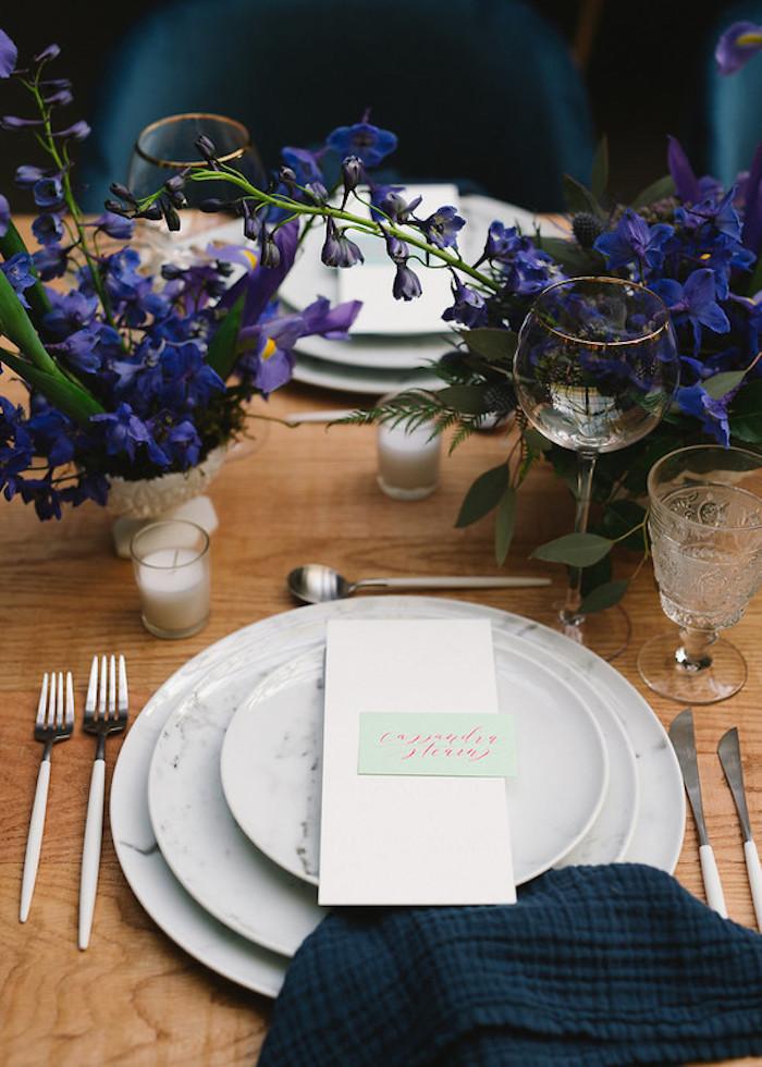 Stilvolle Tischdeko für Hochzeit, blaue und violette Blumen, dunkelblaue Servietten