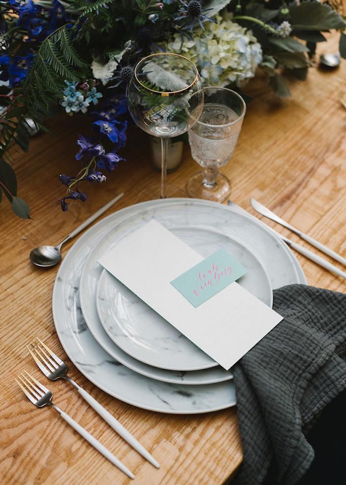 Schöne Idee für Hochzeitsdeko, blaue Blumen, Zettel mit Namen aller Hochzeitsgäste, schwarze Servietten