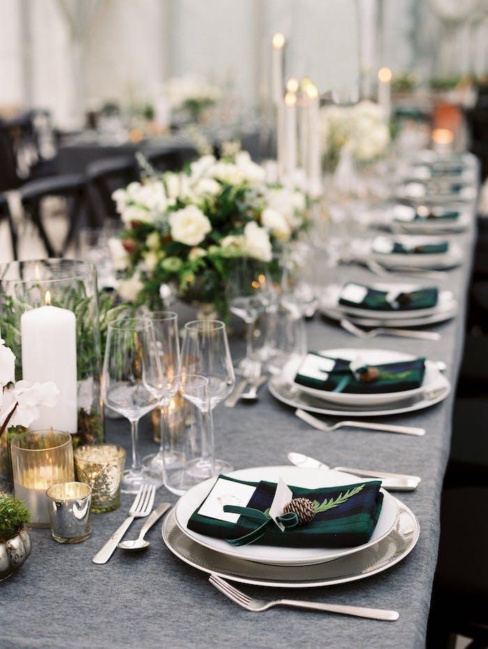 Wunderschöne Tischdekoration für winterliche Hochzeit, weiße Rosen und Kerzen, dunkelgrüne Servietten
