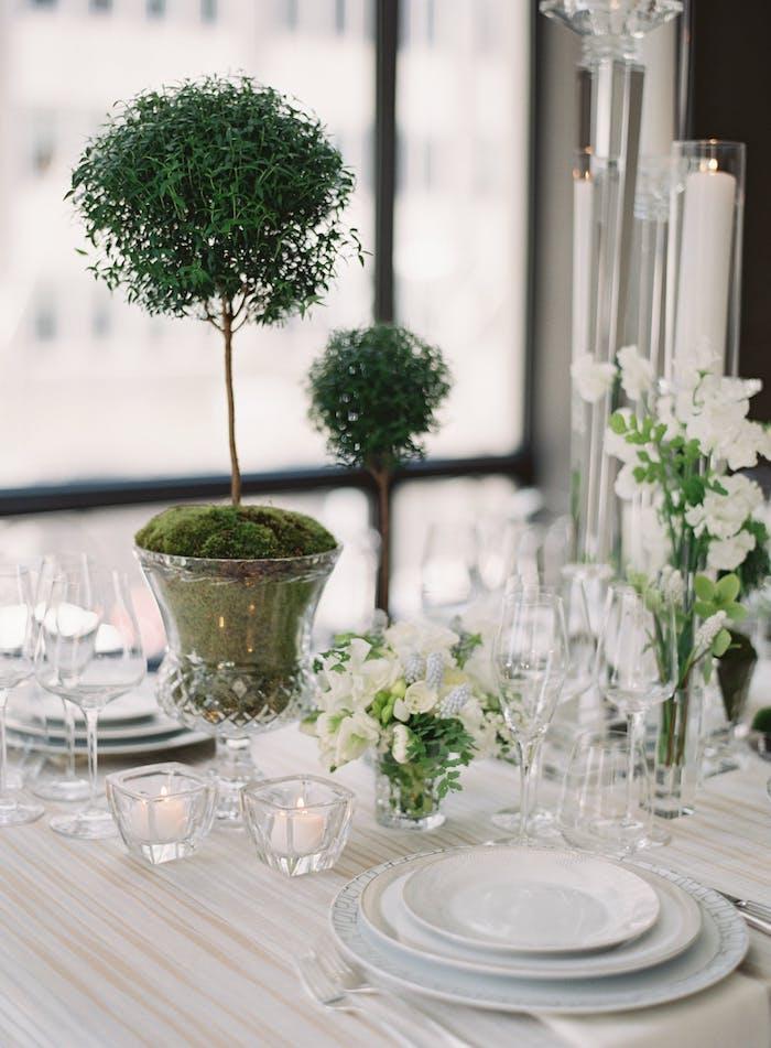 Stilvolle Tischdeko in Grün und Weiß, weiße Blumen und kleine Duftkerzen, Bonsai in Kristallvase