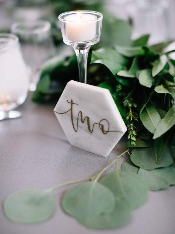 Simple und stilvolle Tischdeko für Hochzeit, kleine weiße Duftkerze, frische Blätter