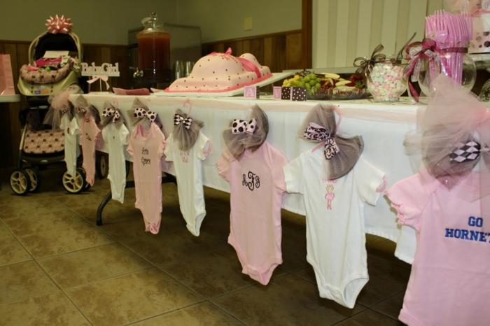 Deko für Babyparty, kleine Klammotchen, eine Torte in der Form von Babybauch
