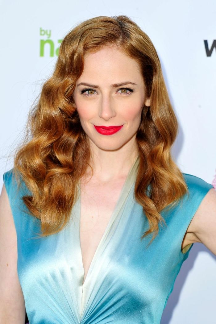 Rey Newman hat ein bezauberndes rotes Haar, blaues Kleid, roter Lippenstift, Langhaarfrisuren
