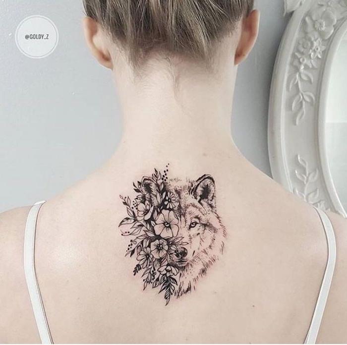 wolf tattoo für frauen, eine junge frau mit einem rücken tattoo mit einem weißen wolf und einem schwarzen wolf und vielen weißen und schwarzen blumen