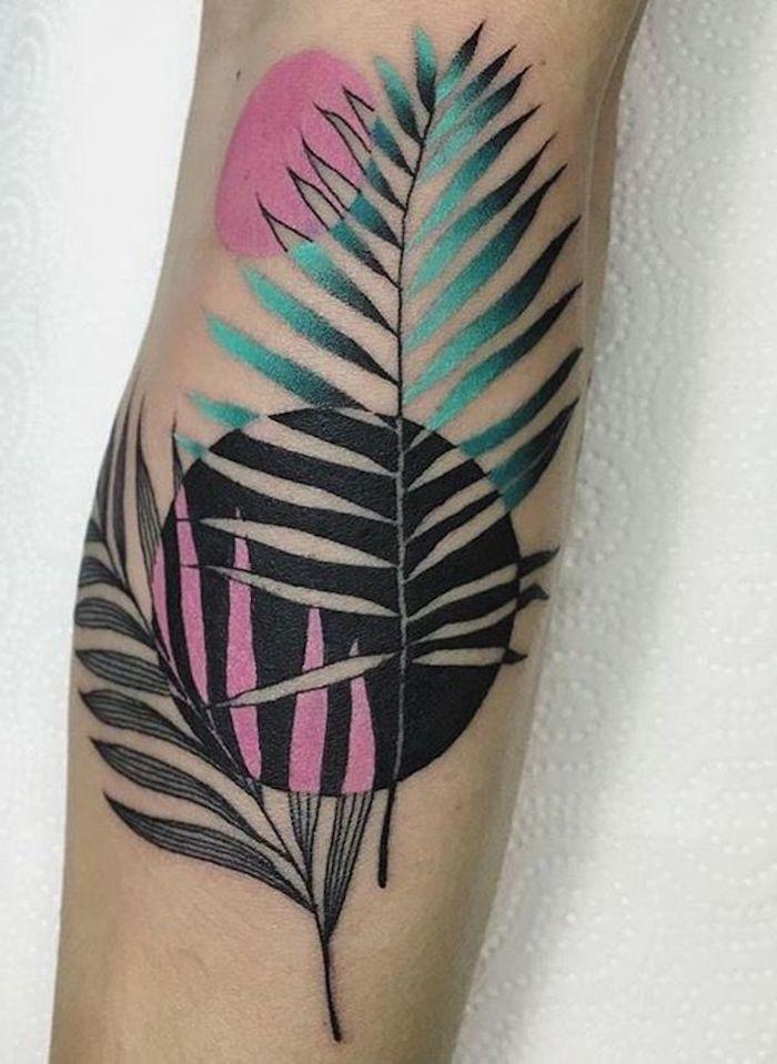 eine hand mit einem farbigen tattoo mit einer schwarzen sonne und mit blättern, watercolor tattoo ideen für frauen
