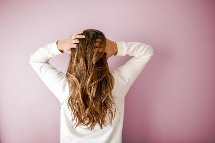 Lange karamellfarbene Haare, schöne Wellen, weiße Bluse mit langen Schultern