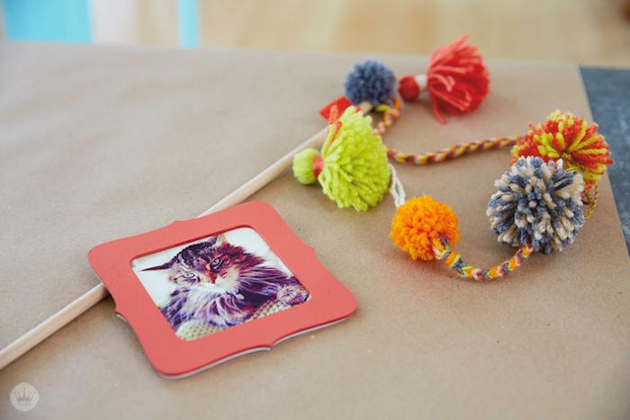katzenspielzeug basteln, orangenfarbener bilderrahmen, angel mit bommeln aus bintem garn