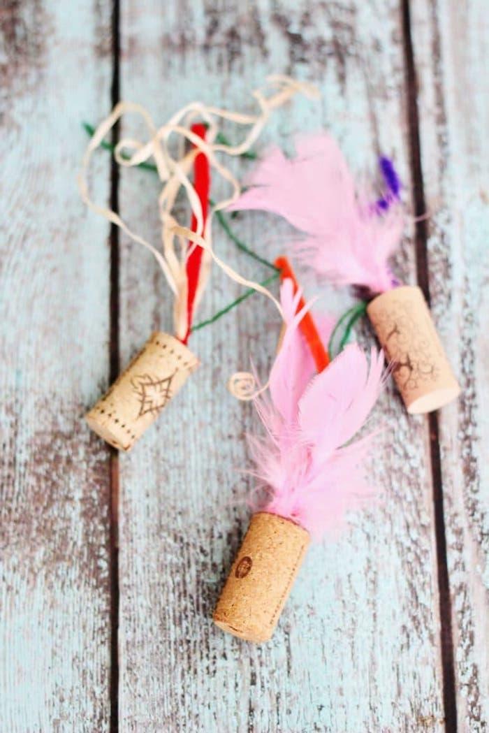 katzenspielzeug beschäftigung, basteln mit weinkorken, rosa feder, schleifen in verschiedenen farben