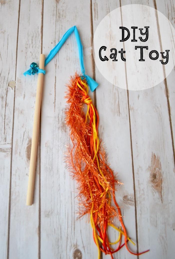 katzenspielzeug beschäftigung, angel aus holzstäbchen, streifen blauem stoff und orangenfarbener girlande
