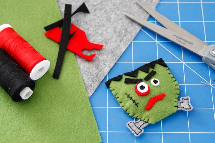 katzenspielzeug diy, roter und schwarzer faden, zombi aus filzstoff nähen, schere