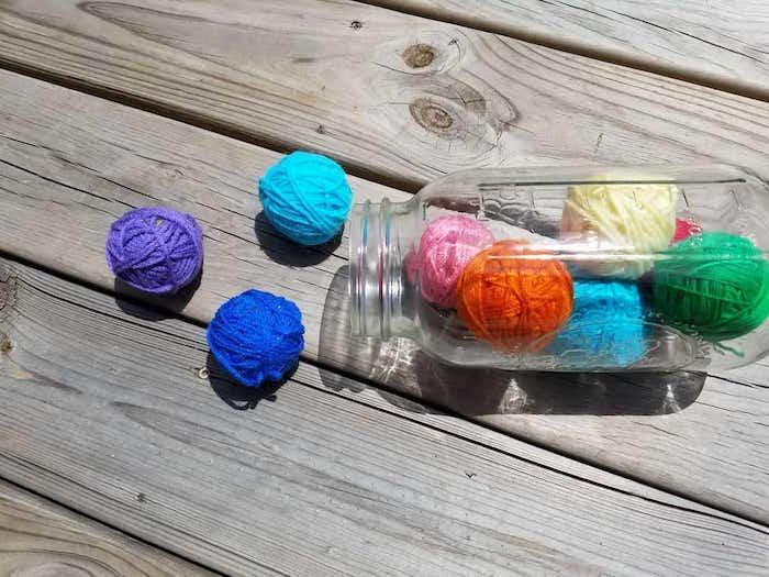 katzenspielzeug selber bauen, großes einmachglas, bunte bälle aus garn, holzboden