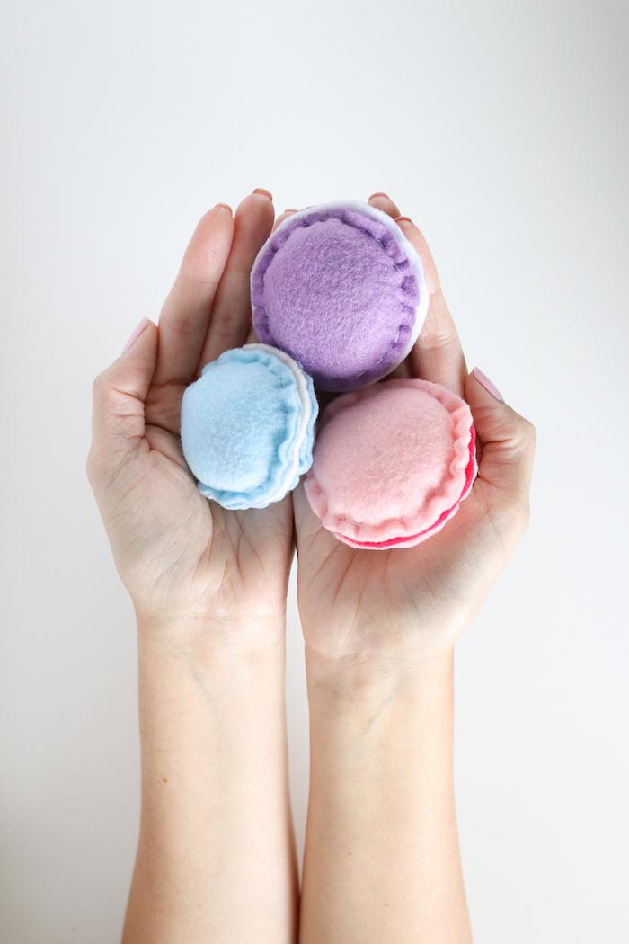 katzenspielzeug selber basteln, selbstgemachte spielzeuge aus stoff in blau, lila und rosa, zwei hände