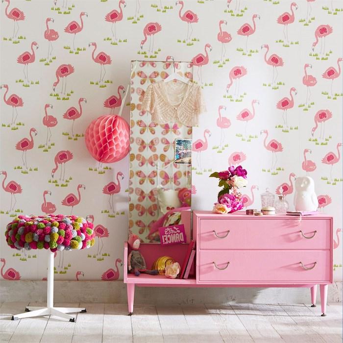 eine wand mit einer weißen flamingo tapete, ein kinderzimmer mit einem pinken schrank und ein spiegel, eine vase mit violetten blumen und ein bunter stuhl