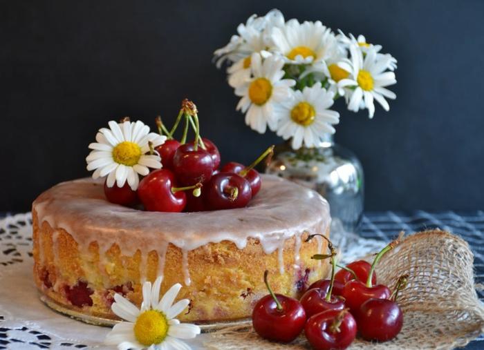 Kirschen, Gänseblumen und ein süßer Kuchen mit lila Creme, einfache Tortenrezepte