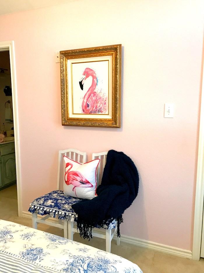 ein weißes bett und zwei stühle mit blauen kissen mit weißen blumen und ein weißes kissen mit einer kleinen pinken flamingo, ein bild mit goldenen bilderrahmen und einer flamingo, flamingo bilder