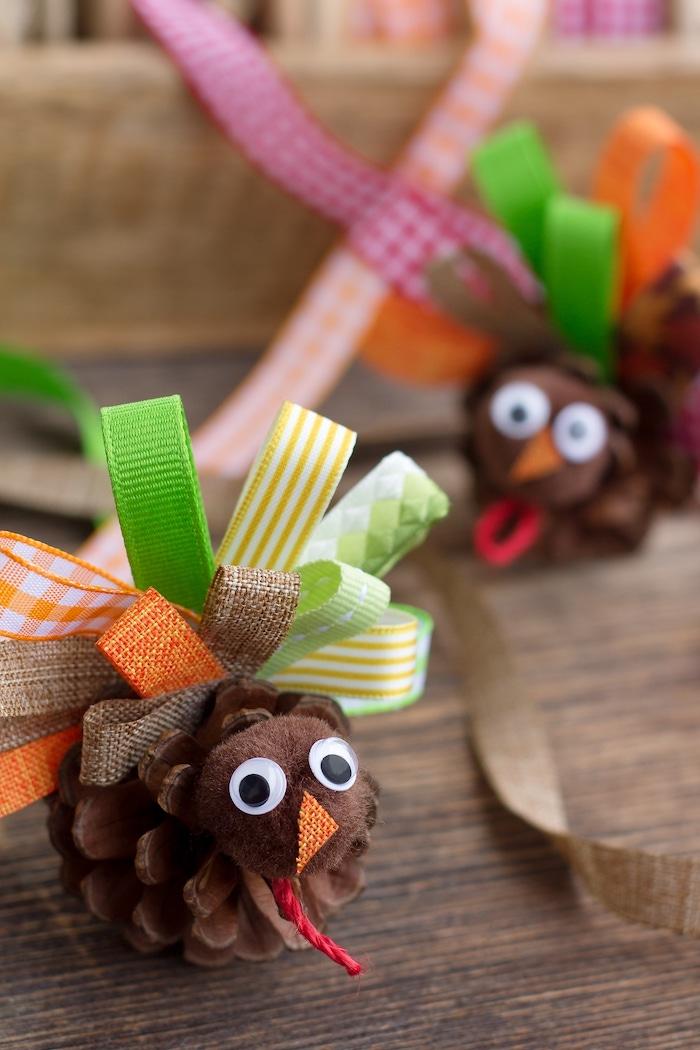ein kleiner brauner vogel aus einem braunen tannenzapfen und mit schwarzen augen und kleinen gefalteten orangen und grünen schleifen