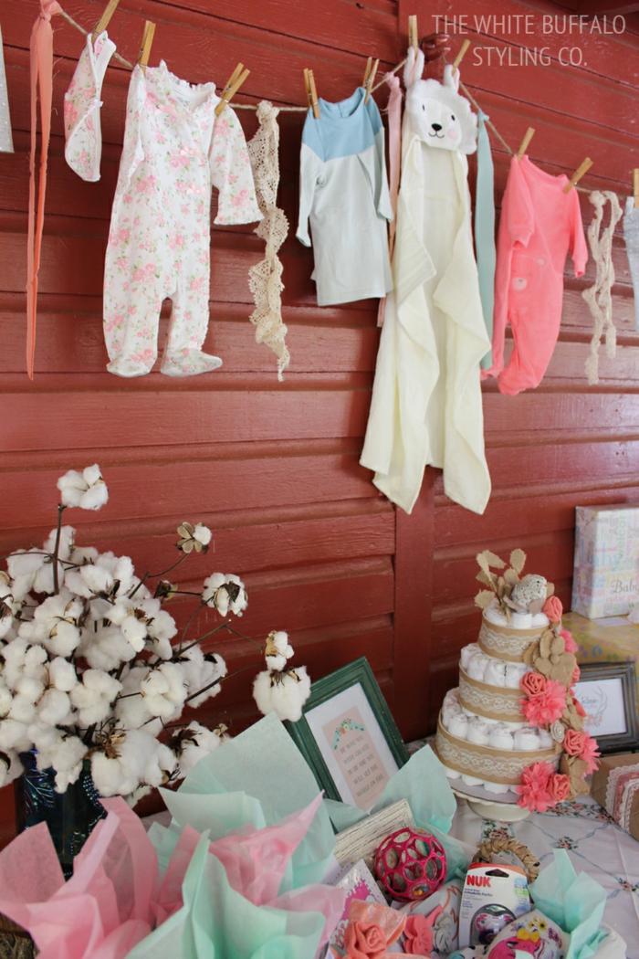 Babyparty Deko mit Geschenken, mit Wäscheklammern gehängt, Windeltorte und weiße Blumen