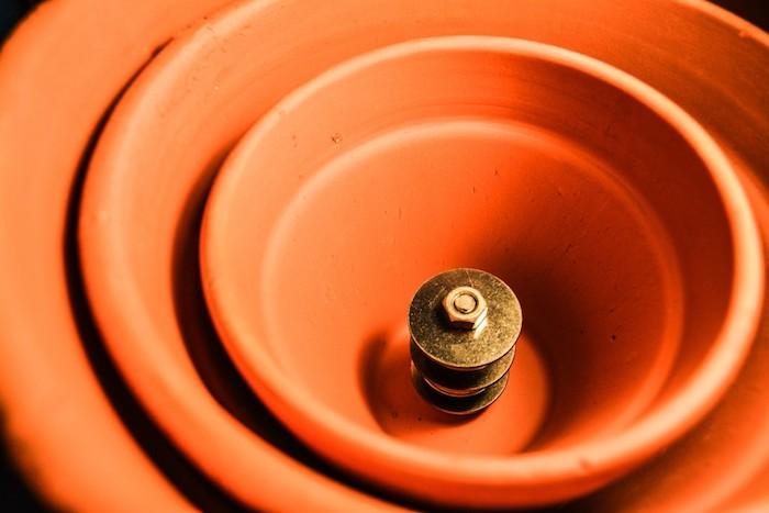 ein diy teelichtofen aus kleinen und großen blumentöpfen aus keramik und mit schrauben und bolzen, teelichtofen selber bauen