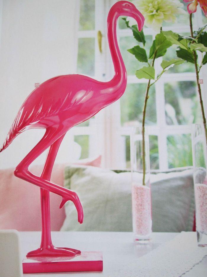 zwei vasen mit weißen und pinken blumen mit grünen blätternm ein weißes fenster und ein sofa mit pinken und grauen kissen und eine statue einer pinken flamingo