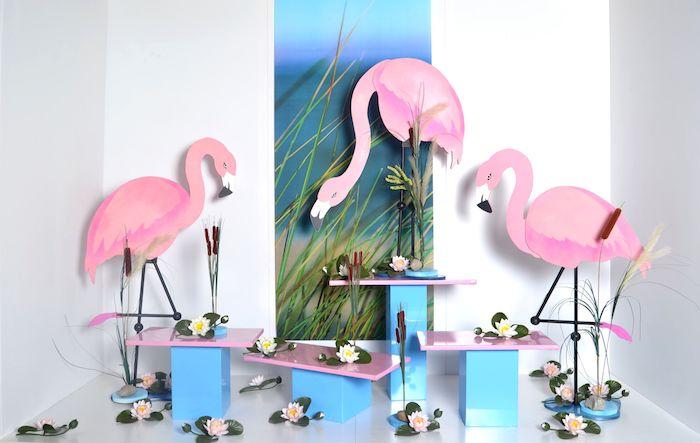 ein wandbild mit meer und grünen pflanzen, drei dekorative große pinke flamingos und weiße blumen mit grünen blättern