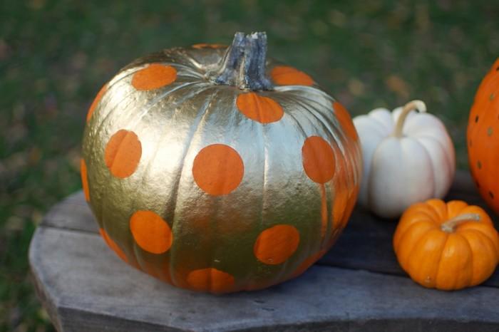 ein goldener halloween kürbis mit großen orangen punkten, kleine orange und weiße kürbisse und ein tisch aus holz, halloween deko selber basteln