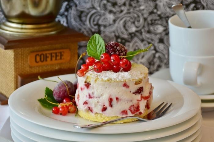 eine weiße Creme mit Erdbeeren Stücke darin, Geburtstagstorte Rezept, kleine Früchte als Dekoration