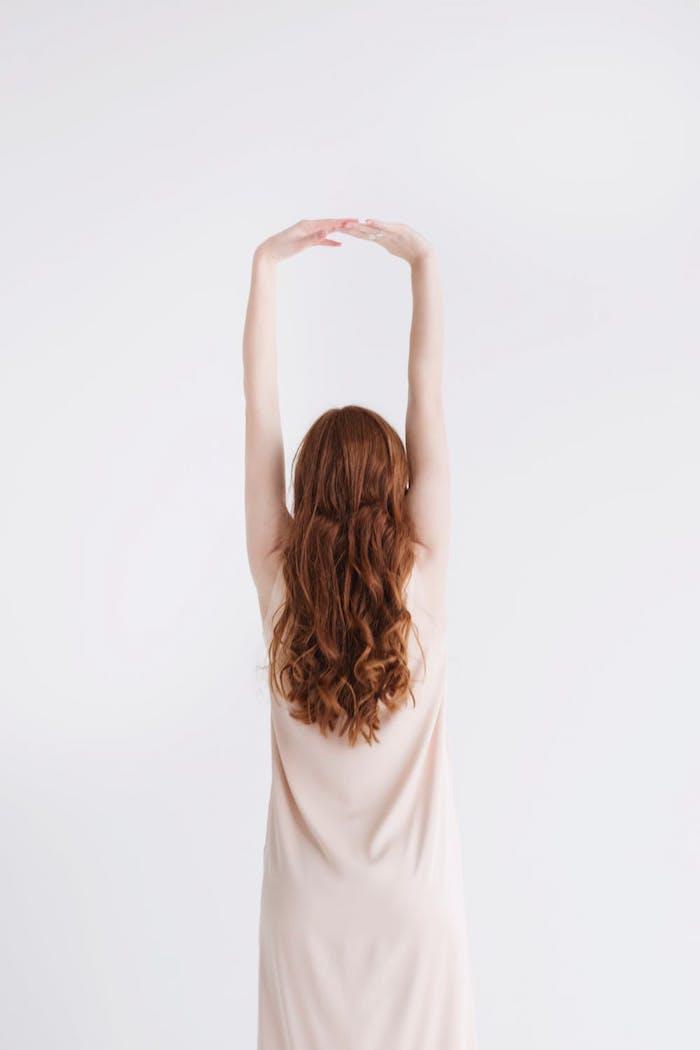 Kupferfarbene lange wellige Haare, heller Hautteint, weißes Kleid