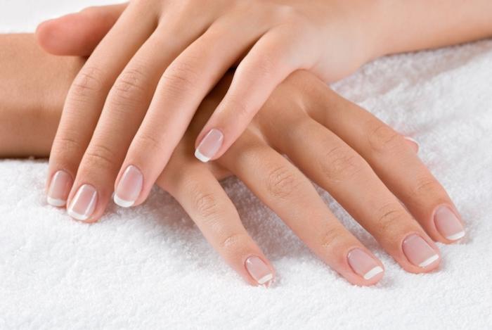 kurze gelnägel french, zwei hände, natürliche maniküre, weißer tuch, handpflege