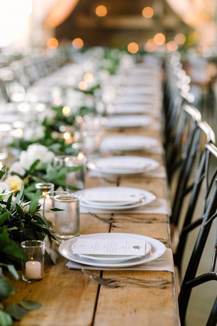 Hochzeitsdeko in Landhausstil, viele Blumen, kleine weiße Duftkerzen, Holztisch mit Altersspuren