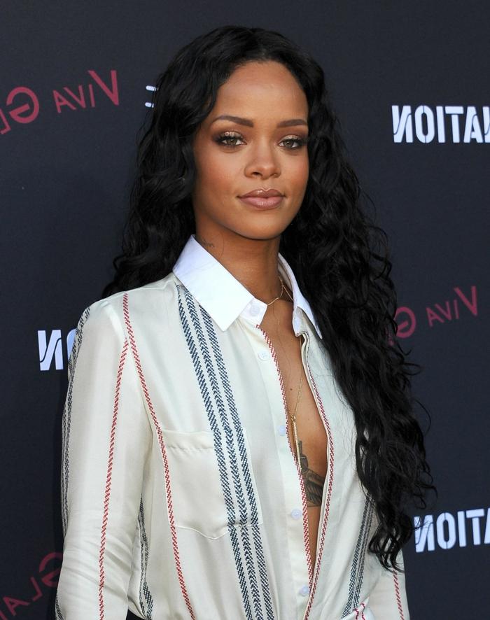 Rihanna mit langen, schwarzen, lockigen Haaren, Langhaarfrisuren, ein weißes Hemd