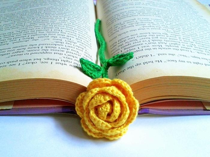 Lesezeichen häkeln, gelbe Rose mit grünen Stängel in einem Buch mit lila Umschlag