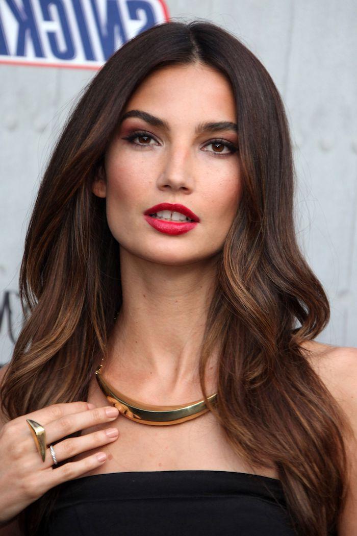 Lange schokobraune Haare mit Mittelscheitel, massiver goldener Schmuck, roter Lippenstift und Smokey Eyes
