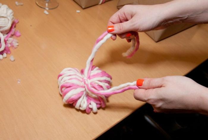 Schritt Vier, binden Sie einen festen Knoten um die Schlinge, rosa und weiße Fäden, Pompons basteln