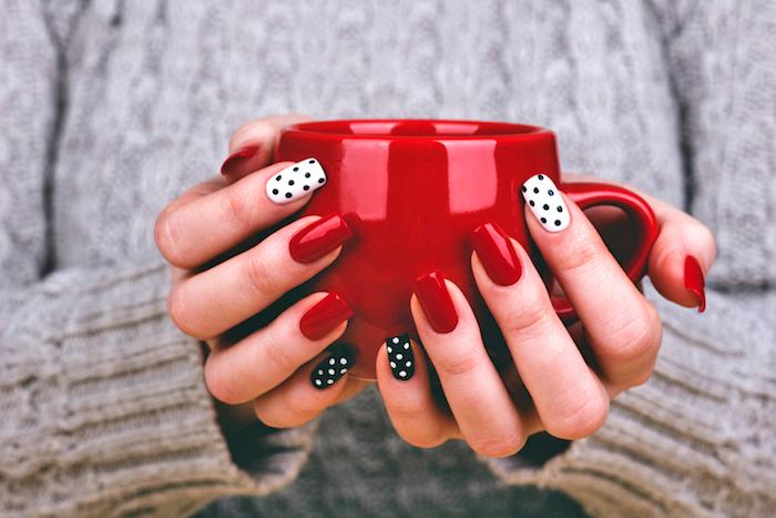 natürliche gelnägel, große rote tasse mit kaffee, grauer pulli, kreative nagelmotive, punkte