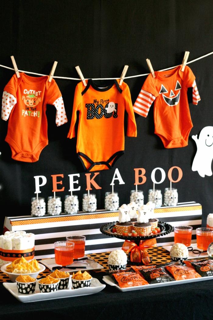 orange Babyklamotten und eine Aufschrift von Kinderspiel, Babyparty Deko