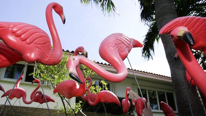 ein weißes haus mit einem garten mit grünen pflanzen und mit vielen pinken dekorativen flamingo, gartendeko ideen, flamingo deko