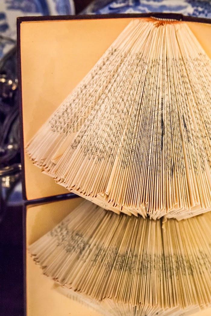 ein nspiegel und ein keliens buch mitn einem schwarzen bucheinband mit vielen gelben alten und gefalteten seiten mit kleinen schwarzen buchstaben, basteln mit papier, papier falten