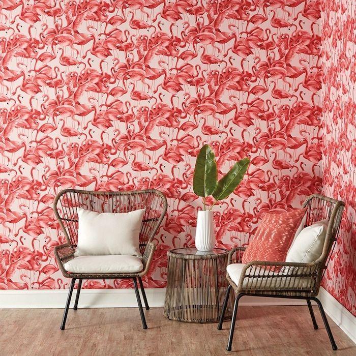 ein zimmer mit einer wand mit einer pinken flamingo tapete, ein tisch mit einer weißen vase mit grünen blättern und zwei stühle aus rattan und mit weißen kissen