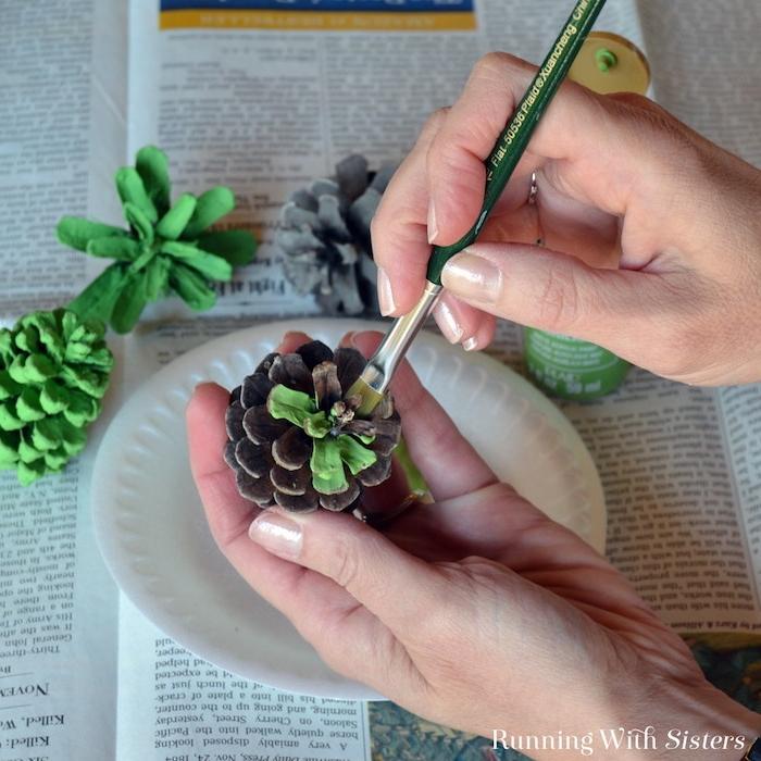 ein tisch mit zeitungen und mit einem weißen teller und mit grünen kleinen bemalten tannenzapfen, kleine braune tannenzapfen, eine hand mit einem ring