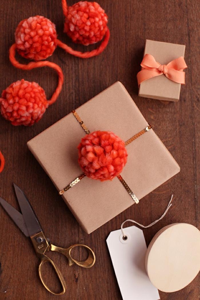 ein Geschenk mit roten Pompons, eine Schachtel mit brauner Verpackung, Basteln mit Wolle