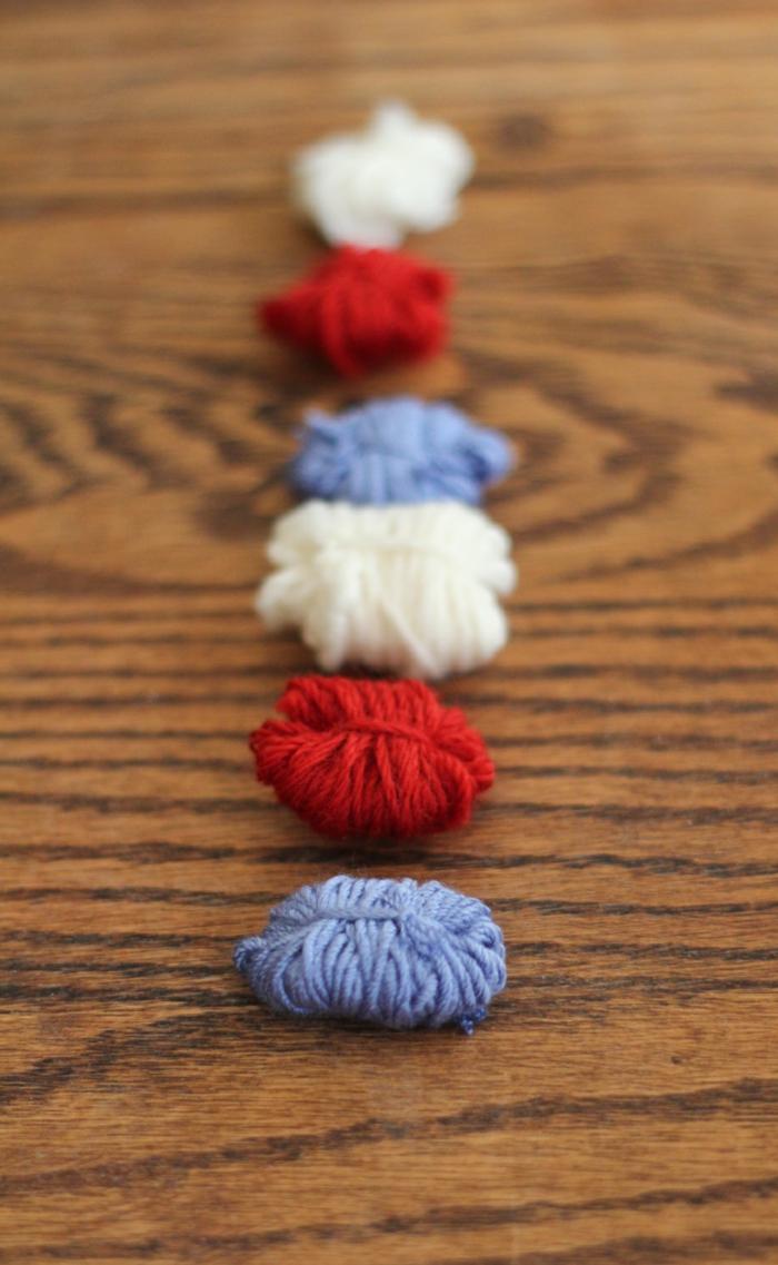 fast fertige Pompons in roter, weißer und blauer Farbe in einer Rahe geordnet, Pompons Deko